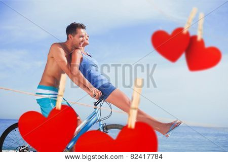 Man giving girlfriend a lift on his crossbar against hearts hanging on a line