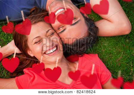 Two friends smiling while lying head to shoulder with an arm behind their head against hearts hanging on a line