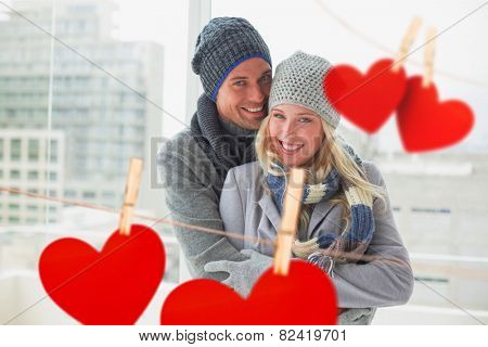 Cute couple in warm clothing smiling at camera against hearts hanging on a line