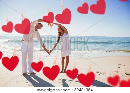 Cute couple forming heart shape with arms against hearts hanging on a line