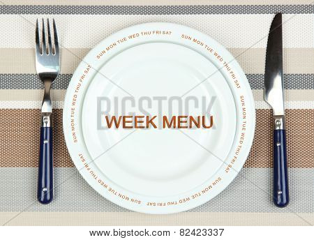 Plate with text Week Menu, fork and knife on tablecloth background