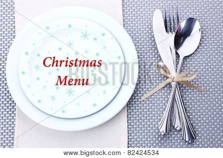 White plates with fork, spoon and knife tied with a ribbon on grey tablecloth