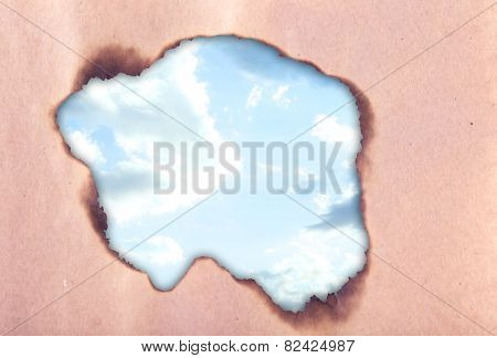 Cloudy sky through scorched hole in paper