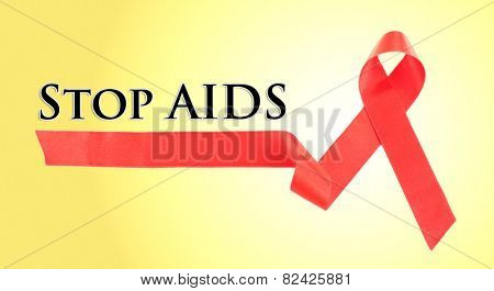 Red AIDS ribbon on yellow background