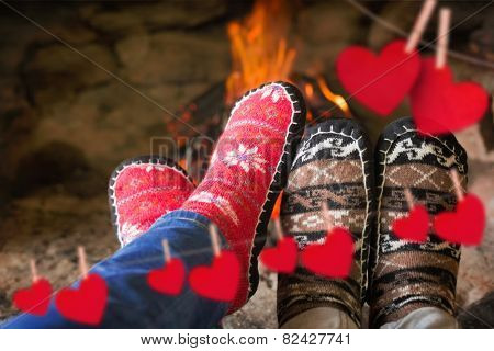 Close up of romantic legs in socks in front of fireplace against hearts hanging on a line