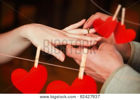 Close up on man putting on ring during marriage proposal against hearts hanging on a line