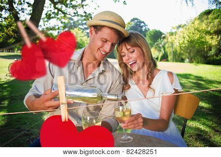 Cute couple drinking white wine together outside against hearts hanging on a line