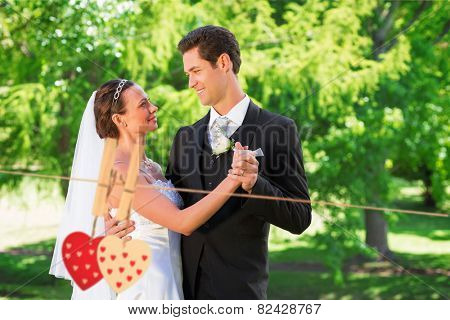Couple dancing on wedding day against hearts hanging on the line