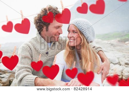 Happy couple sitting together on rocky landscape against hearts hanging on a line