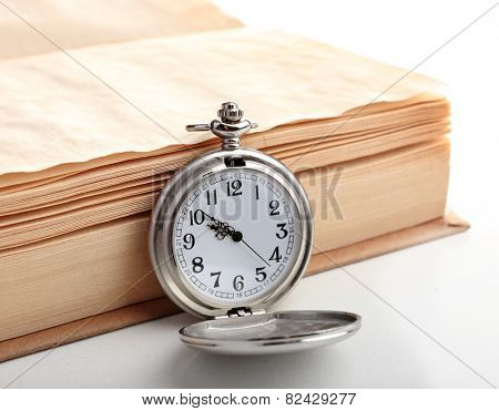 Silver pocket clock and book on white table