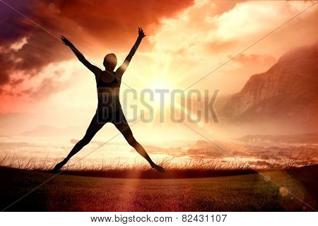 Full length of a sporty young woman jumping against sunrise over magical sea