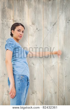 Pretty brunette giving thumbs down against bleached wooden planks background