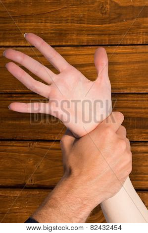 Womans wrist held by man against overhead of wooden planks