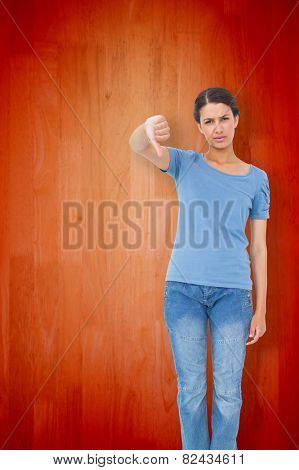 Pretty brunette giving thumbs down against wooden planks background