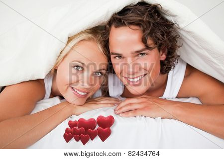 Couple under a duvet against love hearts