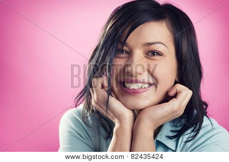 Close up portrait of smiling, happy, girl with hands at chin looking straight, isolated on pink background.