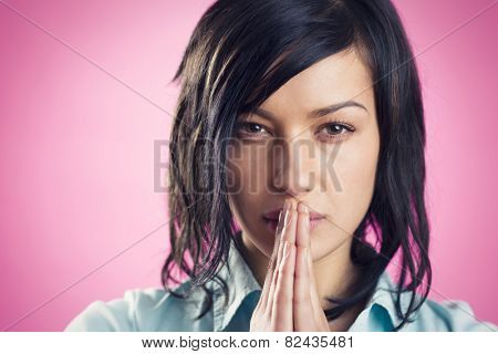 Close up portrait of modern, serious, young girl with folded hands in front of mouth looking straight, isolated on pink background.