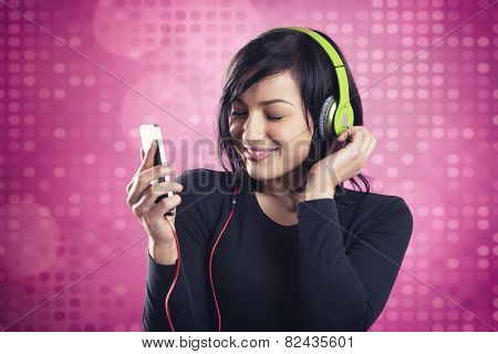 Lovely happy girl enjoying listening to music with headphones and mp3 player with eyes closed, smiling and dancing, isolated on pink disco background.