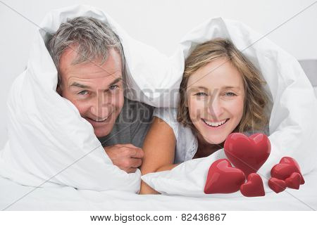 Happy middle aged couple under the duvet against love hearts