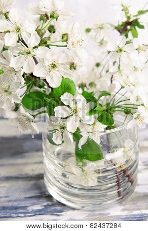 Beautiful fruit blossom in jar on table on grey background
