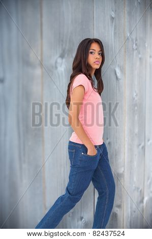 Pretty brunette stepping against bleached wooden planks background