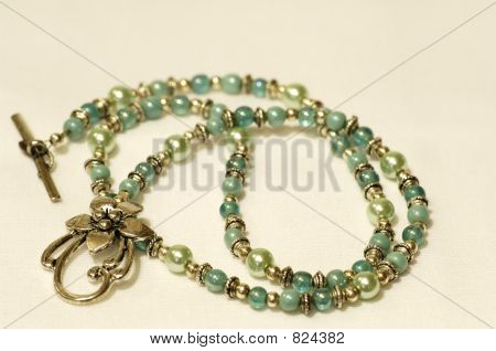Picture or Photo of Beaded necklace lying flat on white background