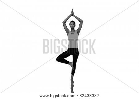 Full length of a fit woman standing in tree pose against mirror