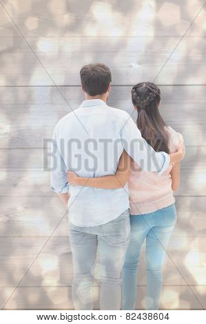 Attractive young couple standing with arms around against light glowing dots design pattern