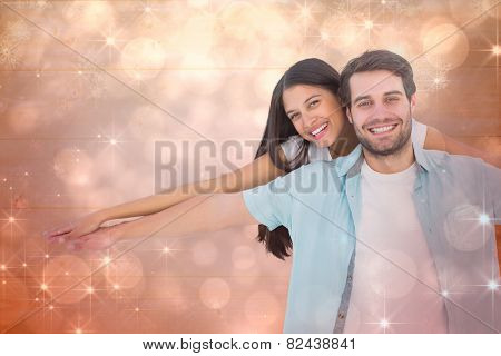 Happy casual man giving pretty girlfriend piggy back against shimmering light design on red