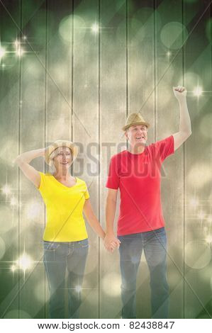 Mature couple walking and holding hands against light design shimmering on green