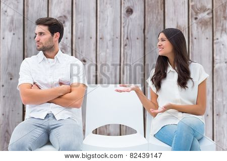 Brunette pleading with angry boyfriend against wooden planks