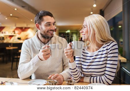 people, leisure, communication, eating and drinking concept - happy couple meeting and drinking tea or coffee at cafe