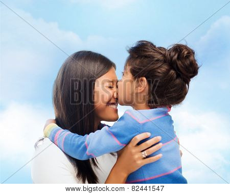 family, children and happy people concept - happy little girl hugging and kissing her mother over blue sky background