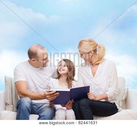 family, childhood, dream and people - smiling mother, father and little girl reading book over blue sky background