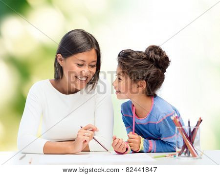 family, children and people concept - happy mother and daughter drawing and talking over green background