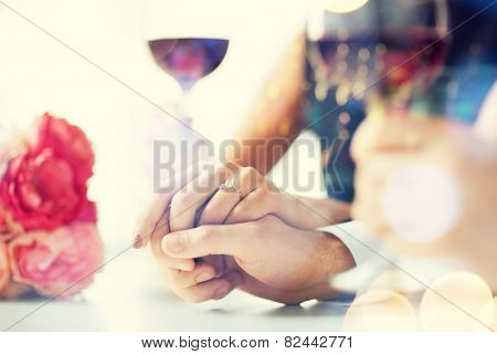 love, family, anniversary concept - engaged couple with wine glasses in restaurant