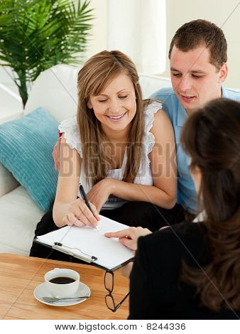 Bright Young Couple Signing A Contract Sitting In Their Living Room