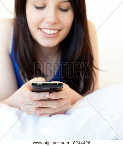 Radiante joven mensajes de texto mientras se está acostado en una cama
