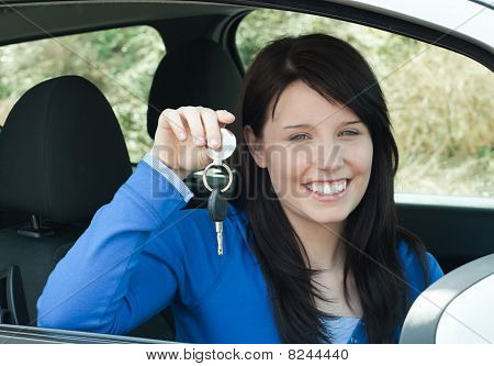 Radiant Teenager Holding Car Keys Sitting In Her New Car