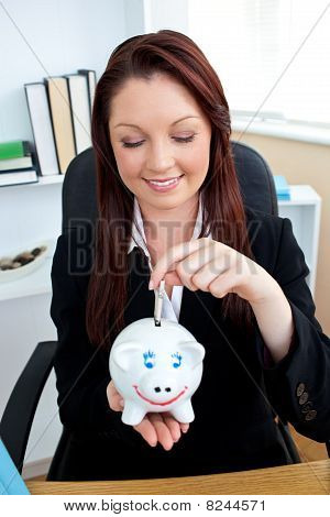 Cute Businesswoman Putting Money In A  Piggybank