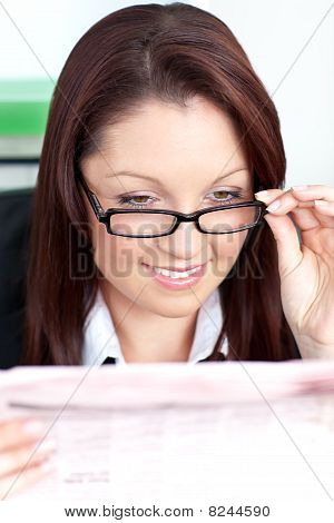 Bright Businesswoman Reading A Newspaper Wearing Glasses