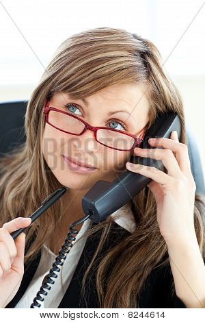 Pensive Businesswoman Talking On Phone Wearing Glasses