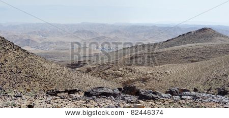 Desert landscape with far Bedouin camp on hazy day
