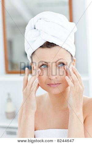 Attractive Young Woman With A Towel Putting Cream On Her Face