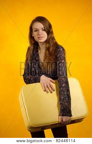 Girl With A Suitcase On Background Of Yellow Wall