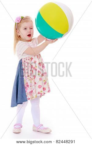 Beautiful girl holding a large inflatable ball.