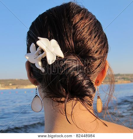 Girl with earrings at the beach at sunset