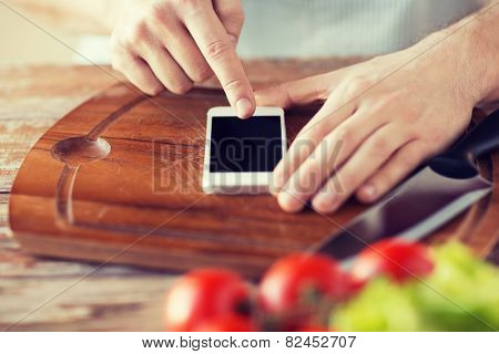 cooking, technology and home concept - closeup of man pointing finger to smartphone