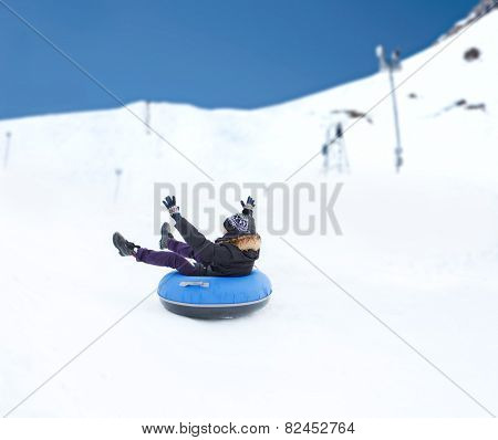 winter, leisure, sport, and people concept - happy teenage boy or young man sliding down on snow tube over mountain background