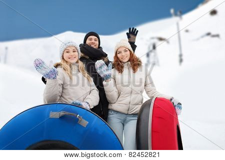 winter, leisure, sport, friendship and people concept - group of smiling friends with snow tubes waving hands over mountain background